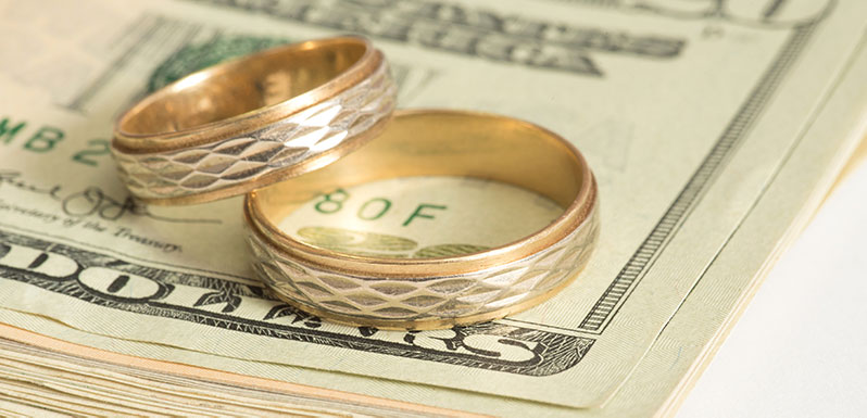 Wedding rings and stack of cash getting divided up in a property settlement case.