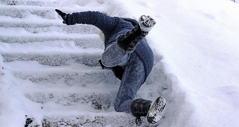Person slipping and falling on icy stairs in Denver, Colorado.