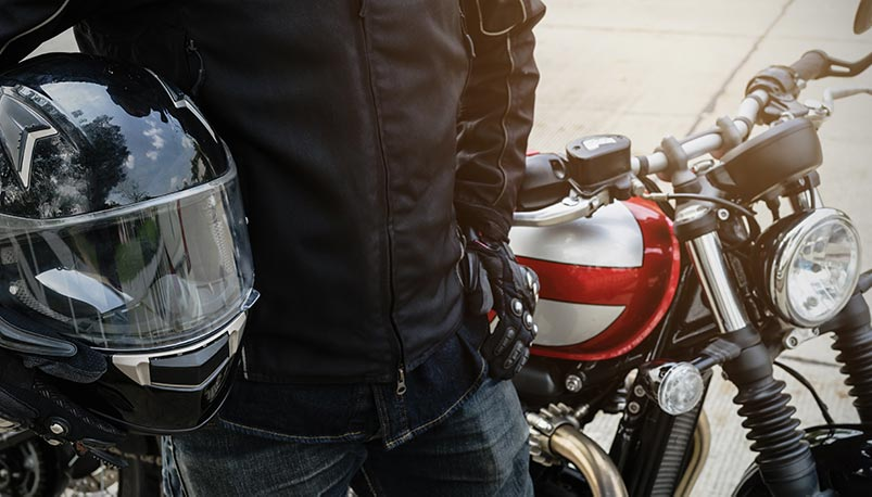 Motorcycle Insurance Laws in Colorado require helmet for riders under 18 like shown in the photos of rider holding helmet with eye protection.