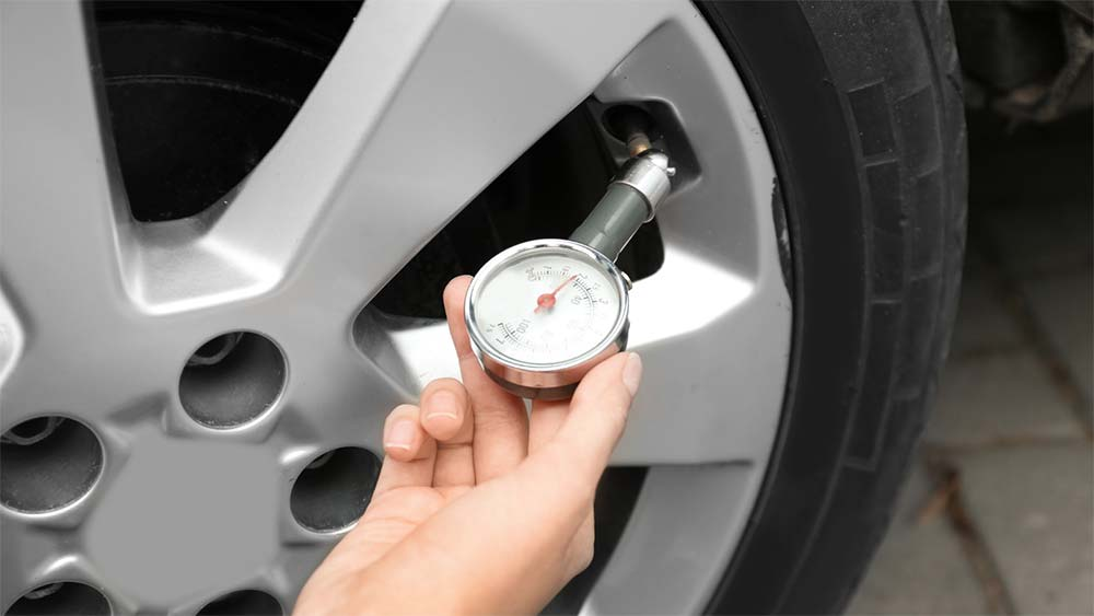 Person checking tire pressure on the car.