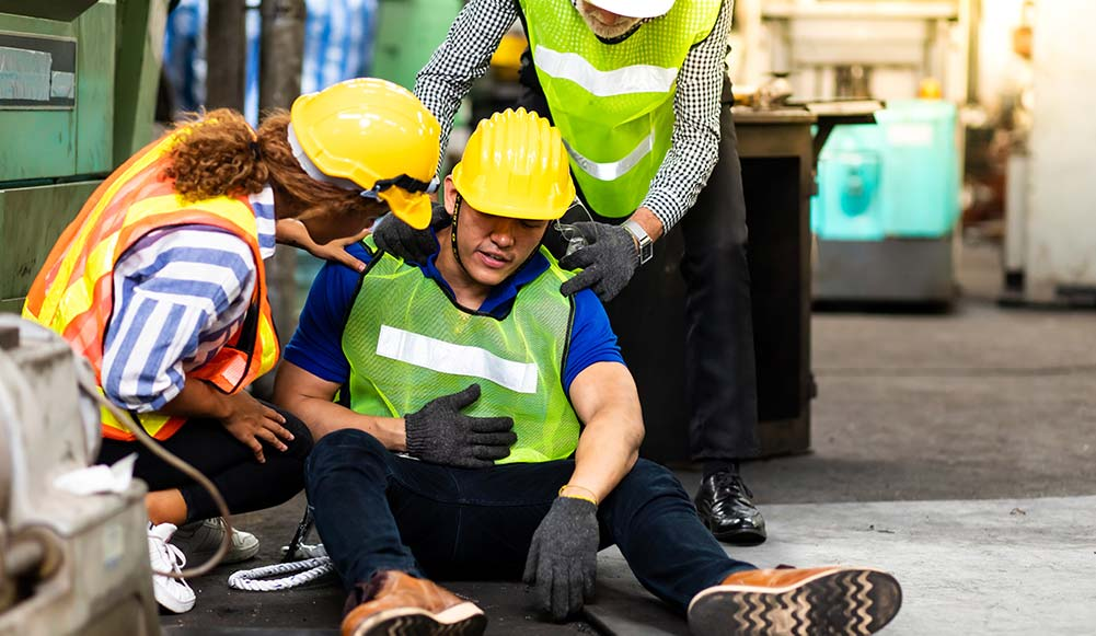 A man injured at work being helped by other workers.