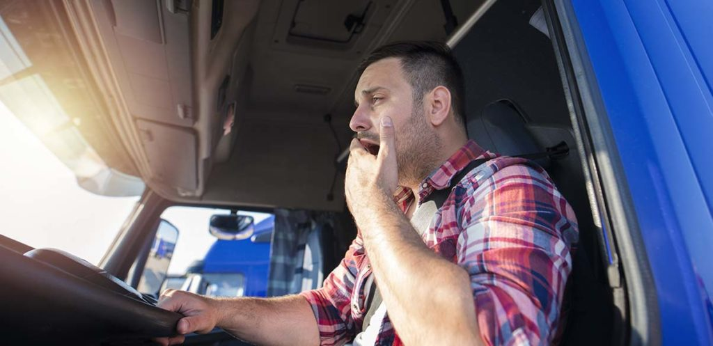 A truck driver that is yawning.