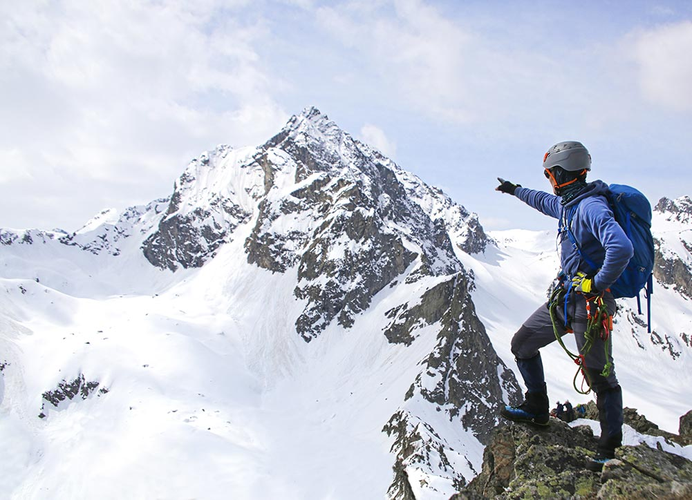 mountain guide pointing to the summit