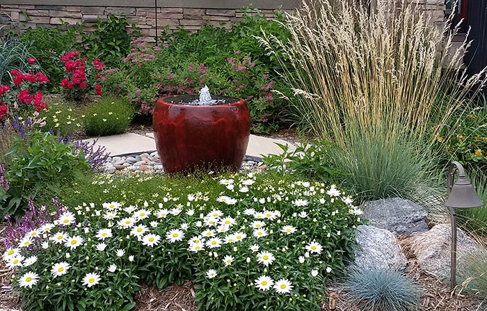 Bubbling pot water feature with colorful plantings.