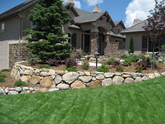 Retaining wall built with large boulders.