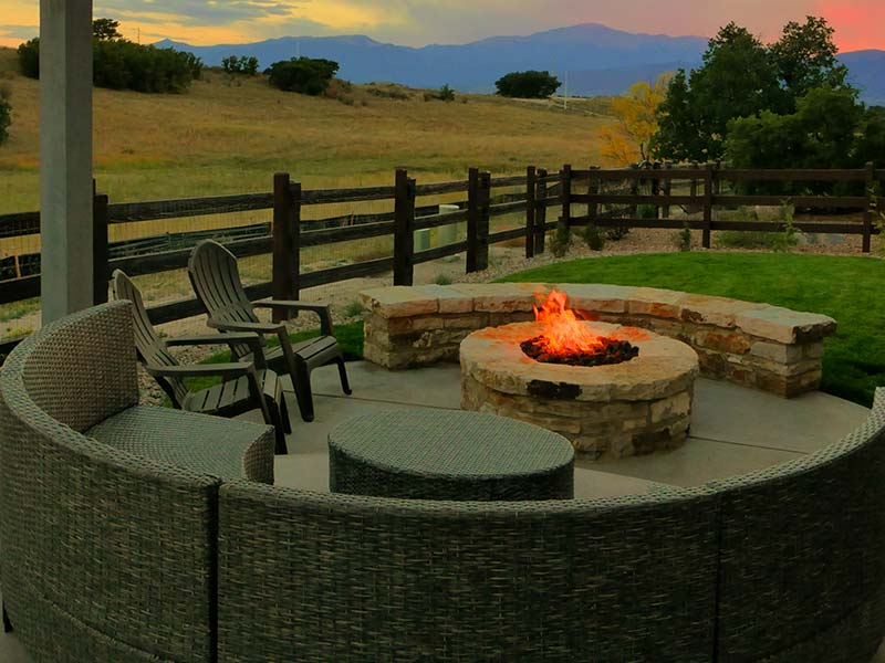 Outdoor living space in Cordera featuring a natural stone fire pit, seat wall, pergola, and outdoor lighting.