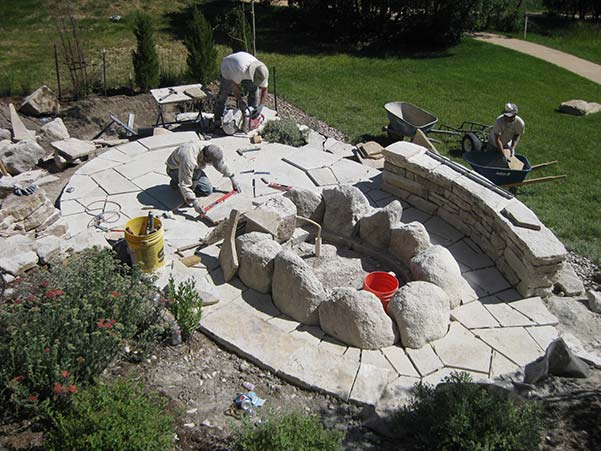 Stone patio with fire pit under construction.