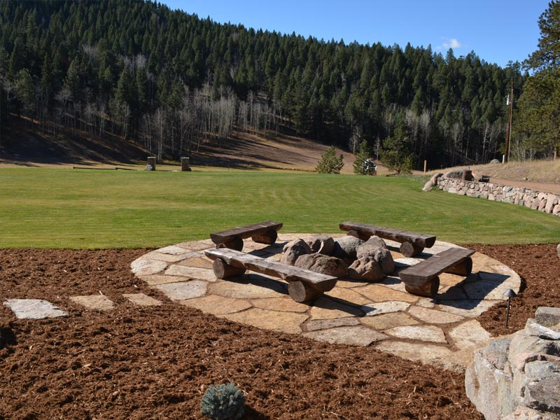 Siloam stone patio with boulder fire pit in the forest.