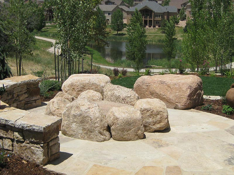 Flagstone patio with a natural gas fire pit constructed of boulders.