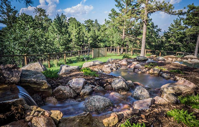 Natural stone water feature with multiple ponds and waterfalls.