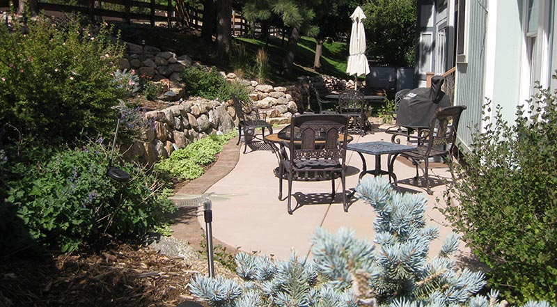 Terraced retaining walls create room for ample patio space and provide attractive planting beds in this small space.