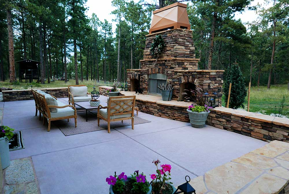 Outdoor patio with fireplace, container plants, dining area, and stone sitting wall.