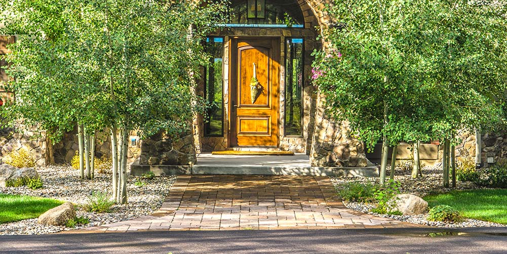 Learning how to install landscape pavers can help you create a front entry way like this Black Forest residence.