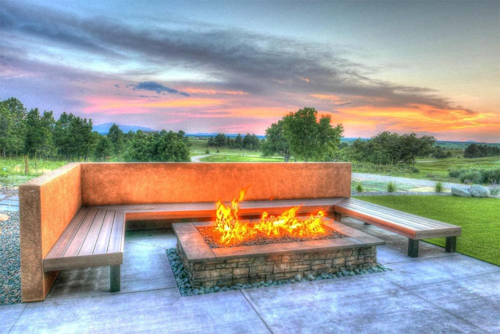 Fire pit with seating in a beautiful residential landscape design.