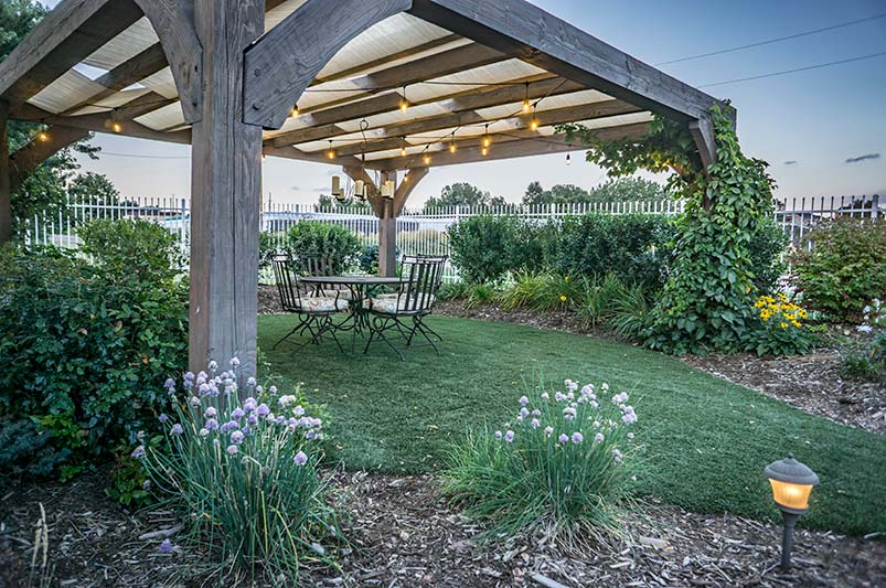 This pergola design has it all, it is stained cedar with shade sails woven through the rafters.
