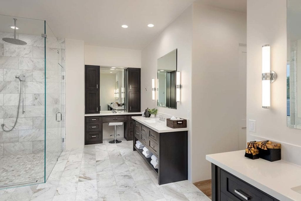Luxury bathroom designed with glass shower, vanity, tile floors, two sinks, and accent lighting.