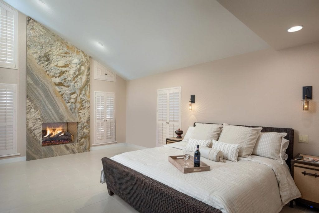 Interior design for master bedroom with vaulted ceilings and gas fireplace.